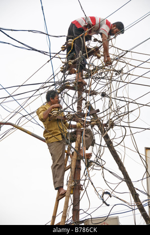 Two men working on wiring. - Stock Image