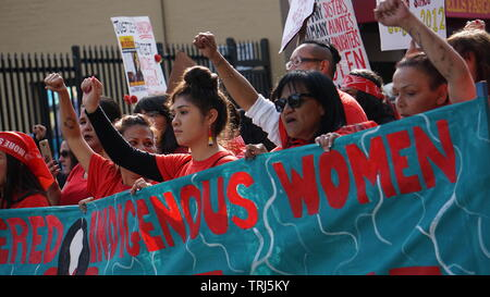 Indigenous or Native American women marching with a banner with fists in air. 2019 Women's March, Market Street, San Francisco, California, USA. - Stock Image