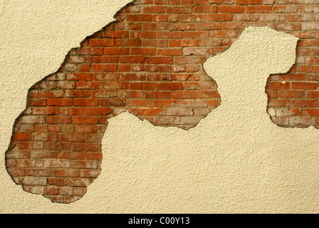 Red bricks showing through a plastered stucco wall of a building - Stock Image