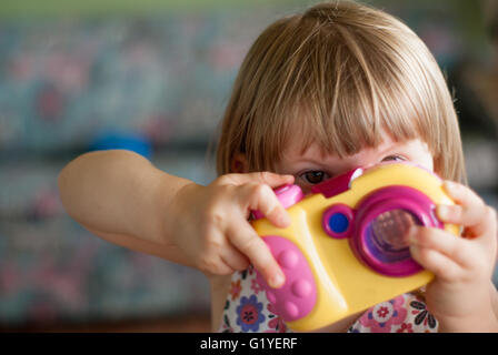 Little girl child playing with camera, taking photo - Stock Image