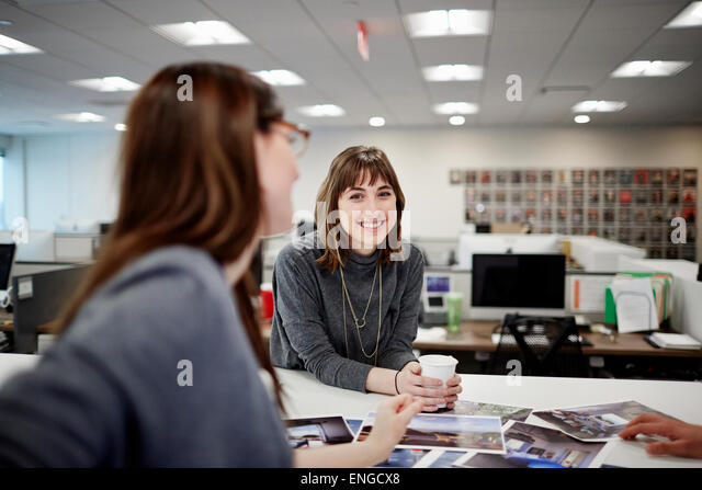 two-women-seated-in-an-office-talking-an