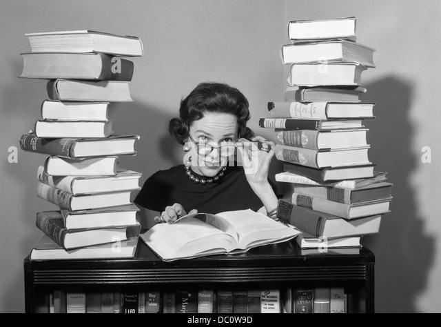 1950s-woman-sitting-between-stacks-of-bo