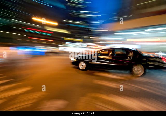 Motion-blurred image of a black sedan driving through Manhattan in New York at night. - Stock Image