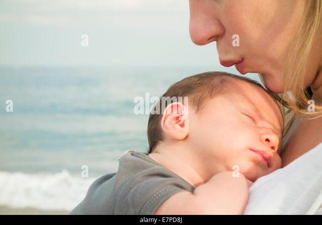 mother-holding-newborn-daughter-on-beach