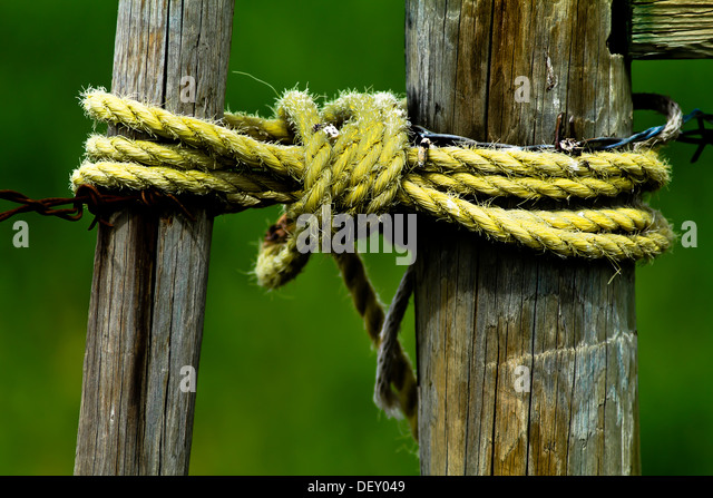 Dramatic, scenic image of rural wooden fence & gate, with rope holding it closed. Suggesting cowboy, ranch, - Stock Image